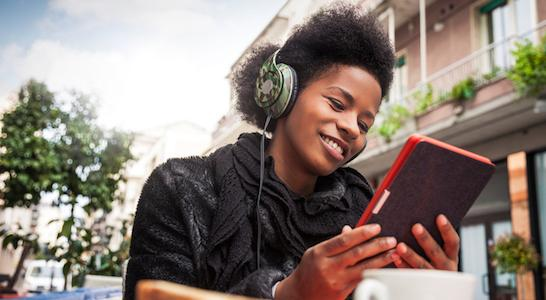 young girl listening to books with headphones on a tablet